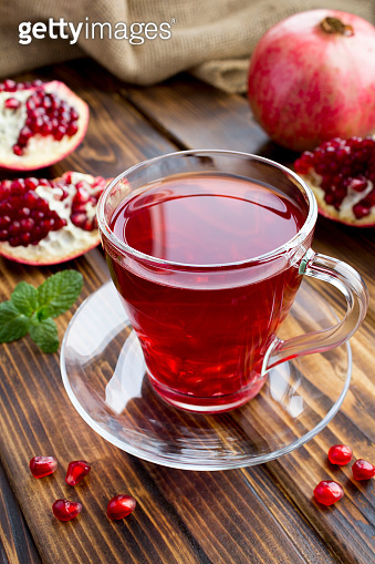 Pomegranate tea in the glass cup the  rustic wooden background