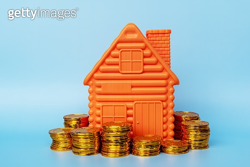 House Model and Stack of Coins on Blue Background