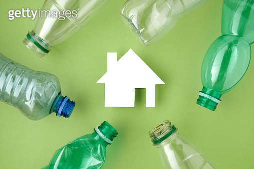 flat lay with plastic bottles and house isolated on green