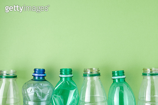 flat lay with plastic bottles isolated on green
