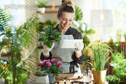 smiling woman in rubber gloves in sunny day using tablet PC