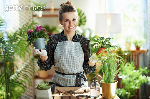 Portrait of happy florist in rubber gloves at home in sunny day