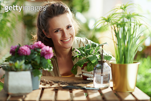 Portrait of smiling woman in rubber gloves at home in sunny day