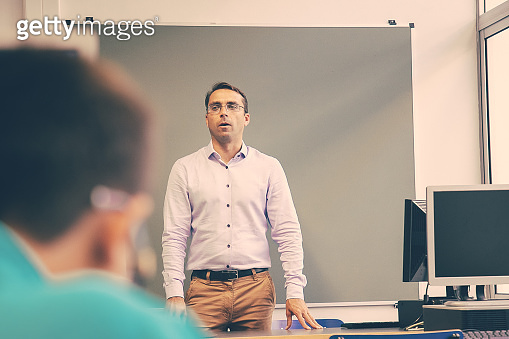 Serious male teacher conducting class