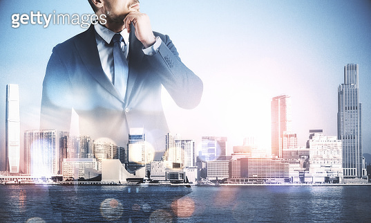 Unrecognizable businessman standing on blurry  city background