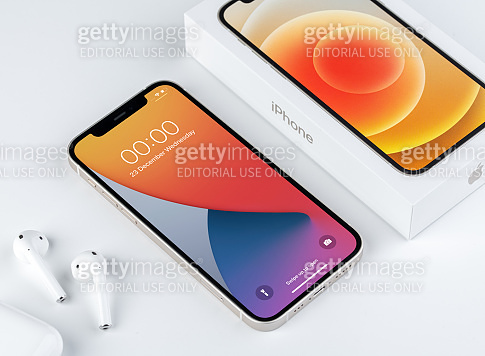 Antalya, Turkey - January 13, 2021: Front view of new iPhone 12 white smartphone and Apple Airpods 2 earphone