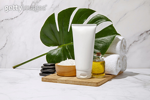 White cosmetic tube with spa element and towel with green leaf on marble background. Blank label for branding mock-up. Natural beauty product concept.