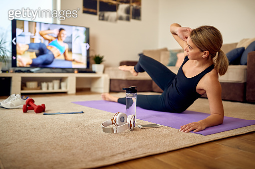 Sportswoman watching exercises class on TV during home workout.