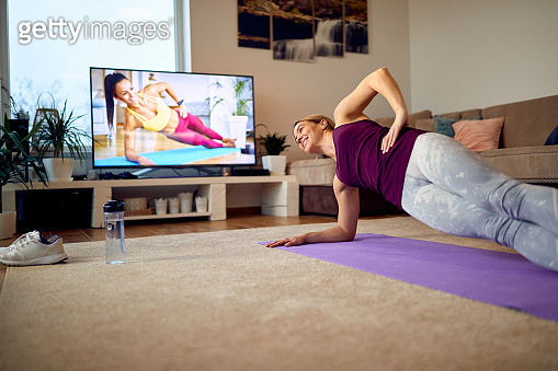 Below view of happy athlete exercising in side plank pose in her living room.