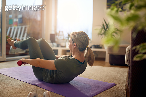 Athletic woman using hand weights while doing sit-ups in the living room.