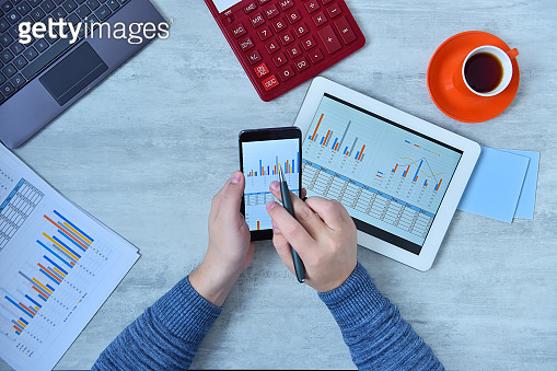 Businessman using mobile phone and checking stock market data.