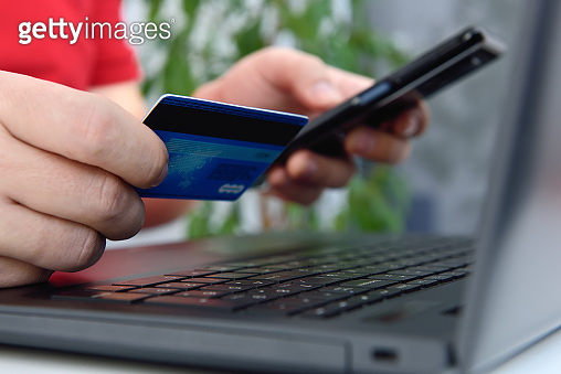 Businessman hands using mobile phone and holding credit card.