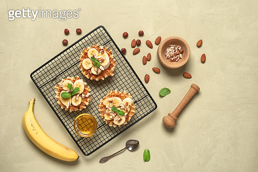Homemade Belgian waffles with banana, nuts and honey. Beige concrete background. Top view, flat lay.
