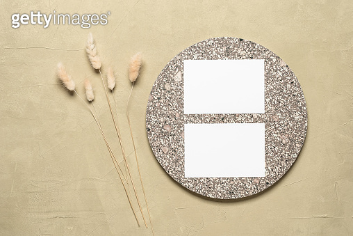 Two business cards mockup with granite elements and fluffy lagurus grass. Beige concrete background. Stationery autumn scene. Top view, flat lay.