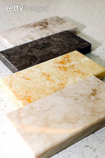Samples of acrylic stone for kitchen countertops. Close-up, vertical photography.