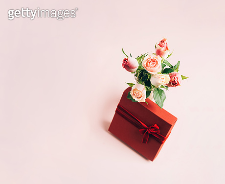 Beautiful fresh roses festive gift box on pastel pink background. Copy space