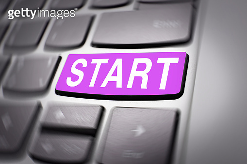Start button colored in pink color on the keyboard with radial blur effect.