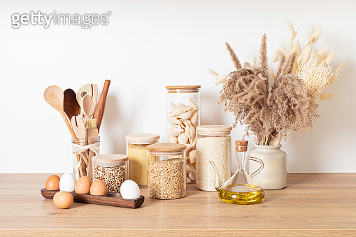 Assortment of cereals and pasta in glass jars and woden kitchen utensils. Zero waste idea