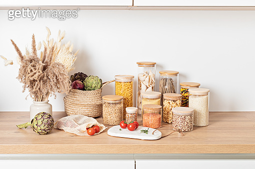 Assortment of grains, cereals and pasta in glass jars and vegetables on wooden table