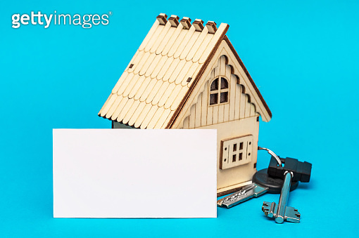 Blank card with model of house and keys from house on blue background. Real estate concept.