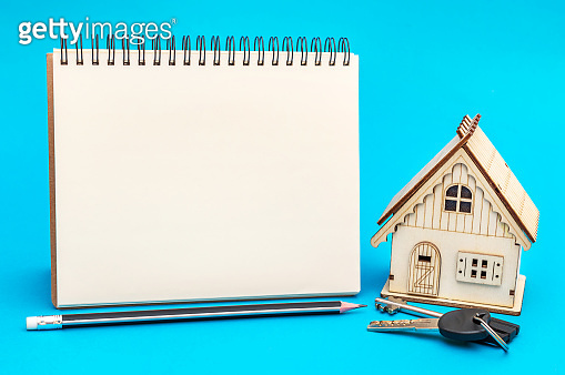 Blank notepad with model of house on blue background.