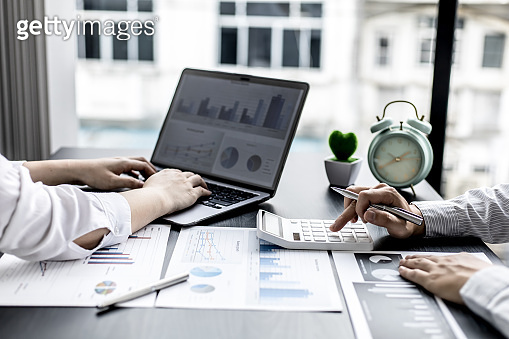 Businesswomen are opening up their laptop's financial information for business partnerships, they are planning to manage their finances and solve common problems. Concept of business administration.