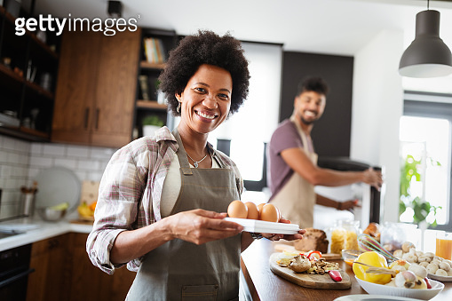 Beautiful couple are hugging and smiling while spending time in kitchen