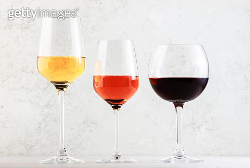 Wines assortment. Red, white, rose wine in wineglasses on gray background. Wine bar, shop, tasting concept