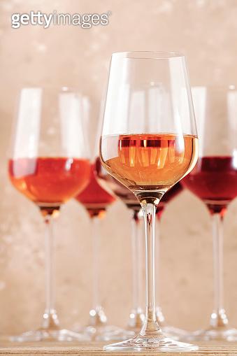 Rose wine glasses on the beige table. Rosado, rosato or blush wine tasting concept, negative space