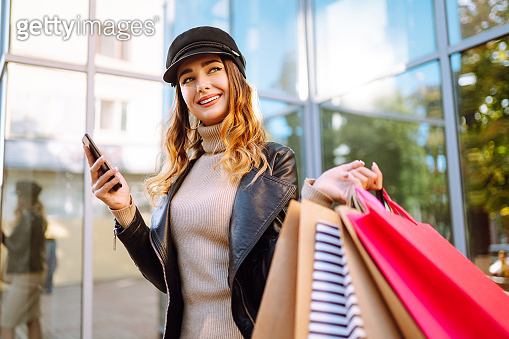 Smiling woman with shopping bags using her phone.