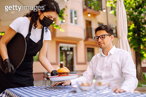 Waitress in protective mask serving delicious food for man in cozy restaurant.