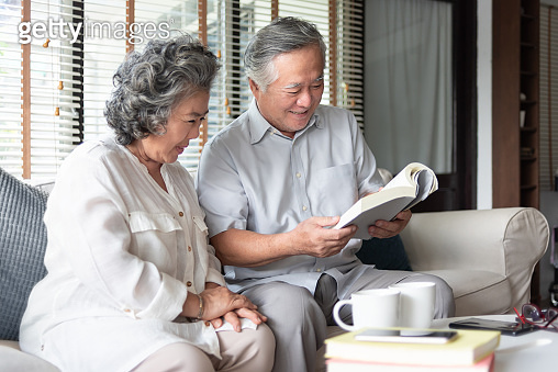 Happy Asian senior couple in love sitting on sofa reading a book together at home.