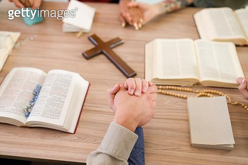 Catholic people praying in Bible study group
