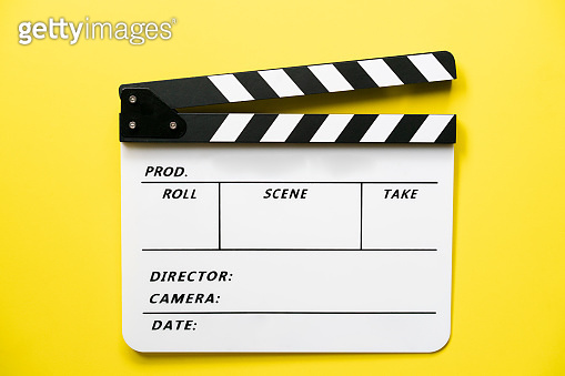movie clapper on yellow table background ; film, cinema and video photography concept