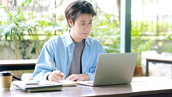 Online education learning, Work from home, Man hand writing on notebook while using laptop computer, Adult male student study online course