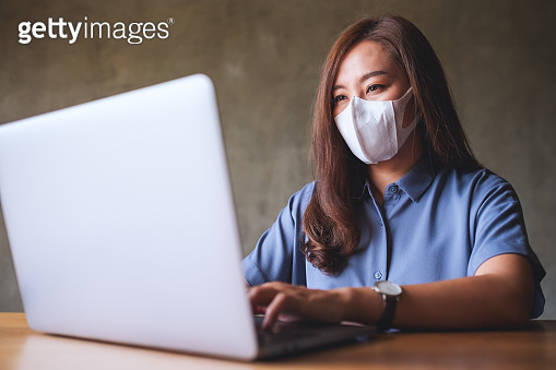 Businesswoman wearing protective face mask while working on laptop computer in office