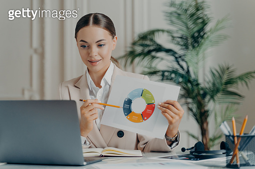 Female economist during internet meeting pointing at financial data