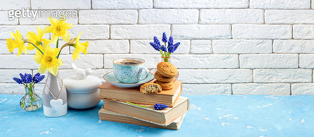 Bouquets of spring flowers, coffee cup, books, cookies on blue table over white brick background. Reading and breakfast. Concept spring, hygge and cozy home interior