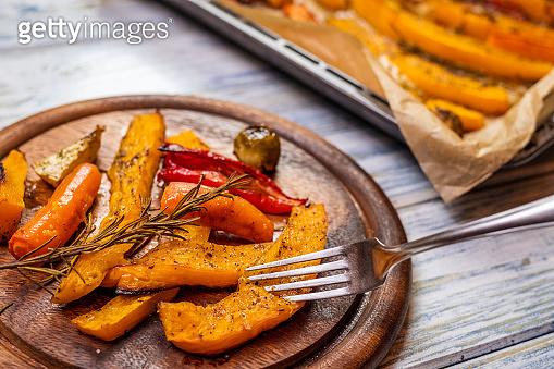 Baked pumpkin hokkaido and roasted vegetable on wooden plate