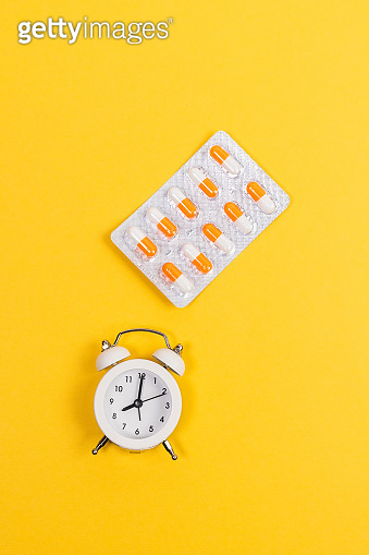 Contraception Day contraceptive pills blister with alarm clock on yellow background. vertical photo