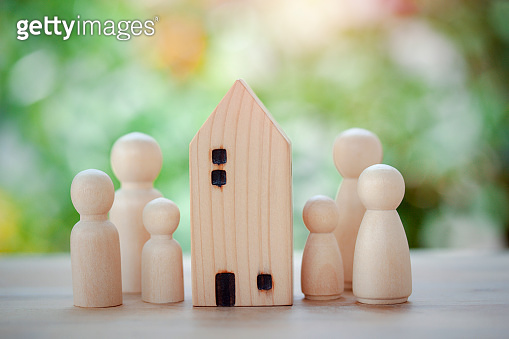Family wooden dolls standing near wooden house for concept strong family, safe zone stay home, loan for purchaseof affordable housing, new house for family and family planning on bokeh background.