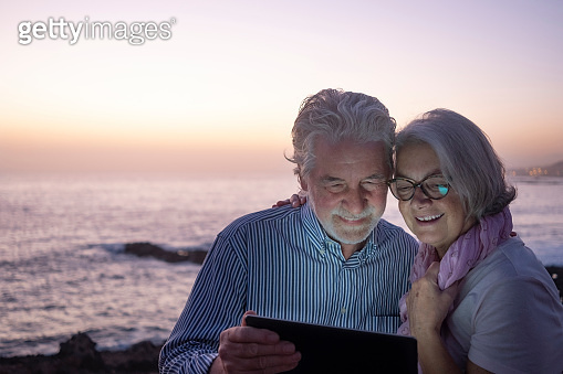 Two attractive senior people white-haired looking at digital tablet in the dusk in video chat with family - sitting on the beach with horizon over water on background. Happy retirement concept together