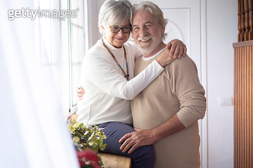 Two beautiful old people hugging each other with love in front of the window. Concept of love and happiness between senior couple