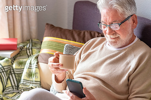 Handsome white-haired elderly man in lockdown at home using his smart phone while drinking a cup of coffee. Bright light from the window. Retired seniors using wireless technology