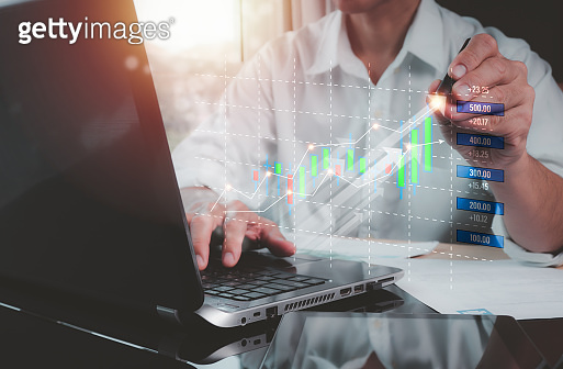 The concept is a stock market investment, businessmen using laptop computers and digital tablets analyzing sales data and economic growth, financial graph chart. Business strategy analysis