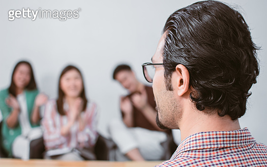 Selective focus of a man training people in a room