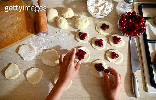 An overhead view of the hands of a pastry chef placing cherries on rolled round molds of dough as one of the stages of making traditional vegan yummy sweet dumplings