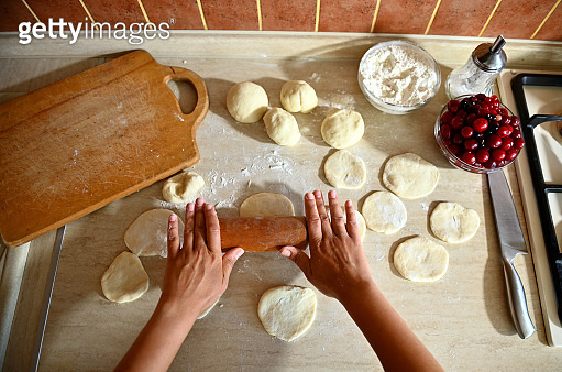 High angle view of female chef hands rolling the dough with a rolling pin on the kitchen counter to make round dumpling molds. Process of cooking dumplings step by step. Close-up, food background