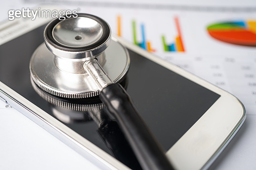 Stethoscope with mobile phone on graph paper, Finance, Account, Statistics, Investment, Analytic research data economy business and technology company concept.