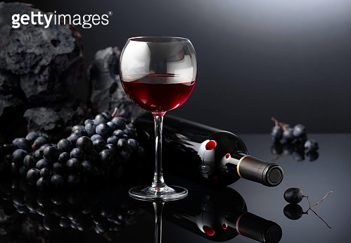 Grapes and red wine on a black reflective background.